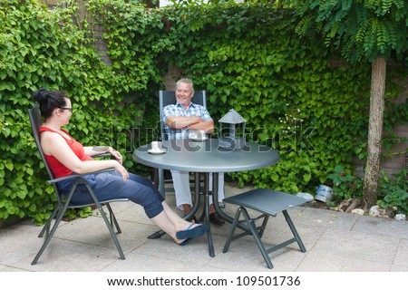 Dutch Daughter and Father sitting at a garden set in the back yard chatting and drinking a hot beverage
