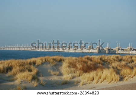 Dutch dike with  wind drifted dunes and at the back the oosterschelde flood barrier protecting the low land against disasters in case of storm surges