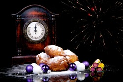 Dutch donut also known as oliebollen, traditional New Year's eve food, clock on midnight and firework over black background