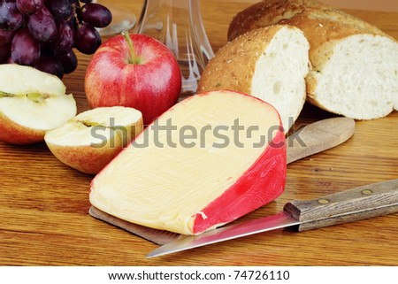 Dutch Edam cheese with fresh fruit and a loaf of bread.