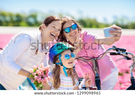 Dutch family riding bicycle in tulip flower fields in Netherlands. Mother and kids taking selfie picture with mobile phone camera on bikes at blooming tulips in Holland. Parents and children biking.