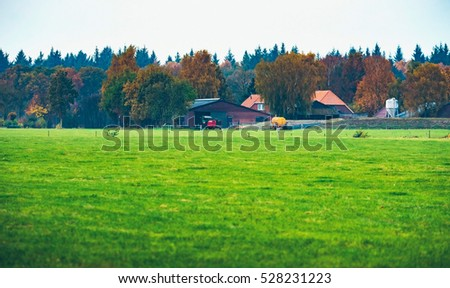 Dutch farm with field in front and autumn forest in the background. Exel. Achterhoek. Gelderland. The Netherlands.