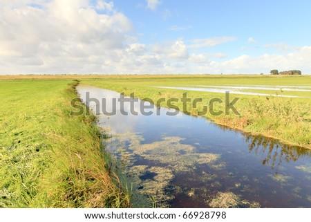 Dutch farmland with canal under blue cloudy sky