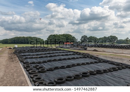Dutch farmland with grass silage covered with black agricultural plastic foil and car tires #1497462887