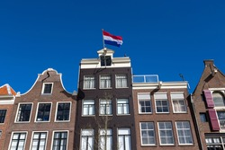 Dutch flag on the canal houses with a blue sky in the center of Amsterdam in the Netherlands.