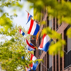 Dutch flag waving in the wind at Kings Day in Tilburg. Red White Blue flag with orange pennant. The Netherlands, Holland