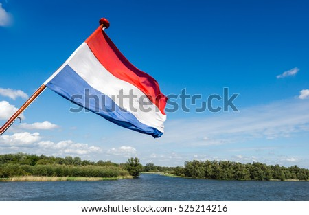 Dutch flag waving on the stern of a tour boat sailing in the waters of a wide creek in the National Park De Biesbosch.