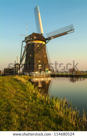 Dutch historic windmill during sunset with a small river in front