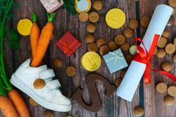 Dutch holiday Sinterklaas background with children shoe, carrots for Santa's horse, gifts, traditional sweets pepernoten and chocolate letter. Flat lay with copy space