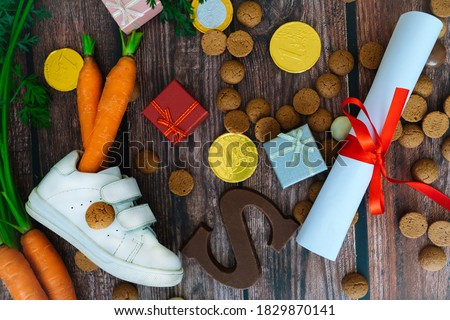 Dutch holiday Sinterklaas background with children shoe, carrots for Santa's horse, gifts, traditional sweets pepernoten and chocolate letter. Flat lay with copy space Stock photo ©