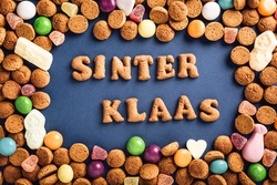 Dutch holiday Sinterklaas background with kruidnoten cookies and traditional hollands sweets. Concept for children party Saint Nicholas day five december with copy space. Top view, overhead.