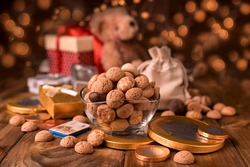 Dutch holiday Sinterklaas. kruidnoten cookies sweets, chocolate and a gift for the child. Children party Saint Nicholas day five december. Christmas bokeh and garlands on the background.