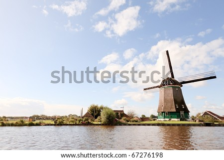 Dutch landscape with canal and windmill under blue cloudy sky