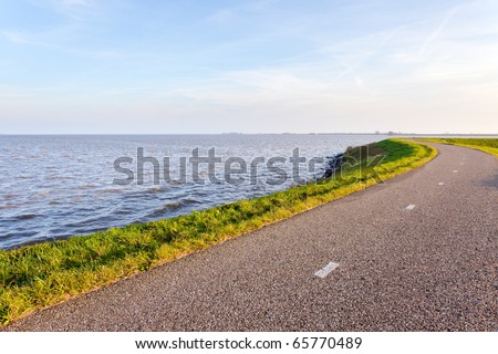 Dutch landscape with dike and road under blue sky