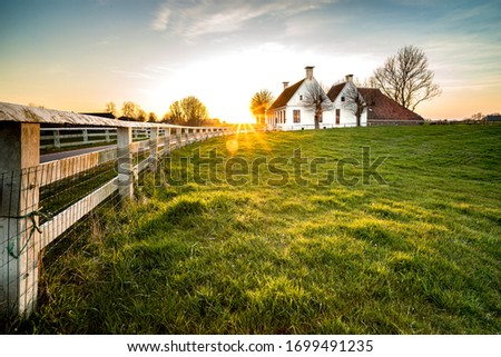 Dutch landscape with historical houses in evening along a curved road with white fence in the country - Groningen, Holland, Europe ストックフォト ©