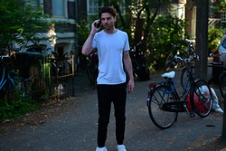 Dutch male student talking on his mobile phone while standing in front of his student house in a traditional street