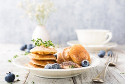 Dutch mini pancakes called poffertjes with blueberries and thyme, sprinkled with powdered sugar. Healthy food concept with copy space.