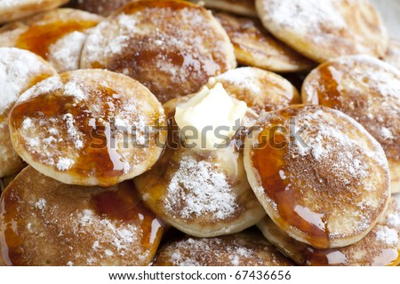 Dutch mini pancakes, or poffertjes, with butter, syrup and powdered sugar.  background.