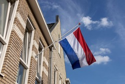 Dutch national flag hanging on the exterior facade of a modern building during the European soccer championship with vibrant blue sky and clouds in the background