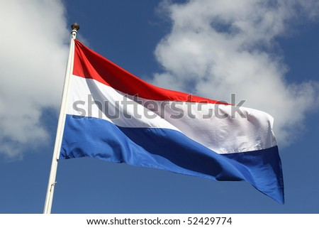 Dutch national flag on liberty day against blue sky with clouds - stock photo