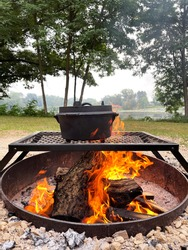 dutch oven on stand over a campfire next to a pond