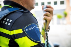 Dutch police officer, with portable or radio. Focus on badge with logo