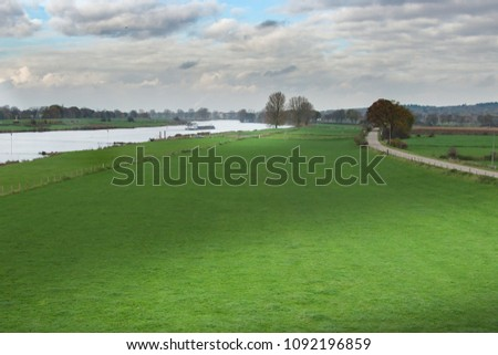 Dutch River landscape scene with nice sunlight spot on the grass in front #1092196859