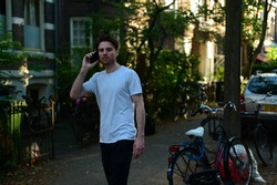Dutch student talking on his mobile phone while walking in front of his student house in Amsterdam, the Netherlands.