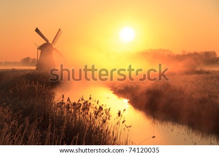 Dutch sunrise with traditional windmill and a canal in the spring fog.