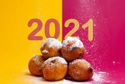 Dutch traditional delicacy for New Year's Eve called 'oil balls' with divided background having 20 and 21 numbers above and behind