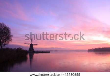 Dutch windmill at a lake during cold and colorful sunset.