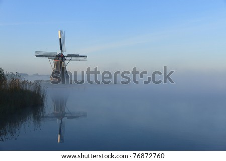 Dutch windmill at a lake in the fog.