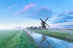 Dutch windmill by river at sunrise, Holland
