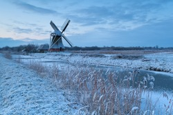 Dutch windmill by river in winter, Netherlands