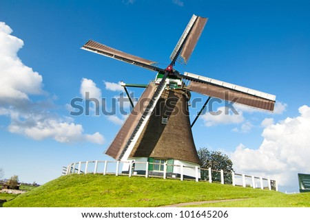 Dutch windmill in fresh green and blue sky