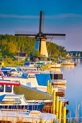 Dutch Windmill In Front of The Canal With Moored Motorboats at Marina Located in Traditional Village in The Netherlands. Shot at Kinderdijk During Golden Hour. Vertical Shoot