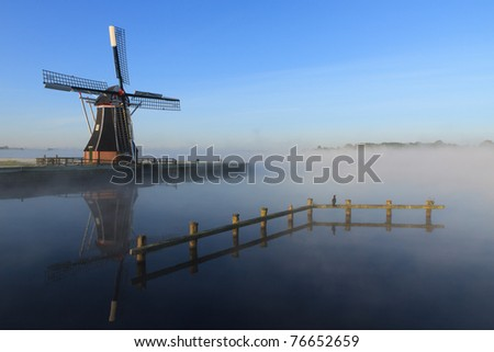 Dutch windmill in the fog at a lake in Holland.