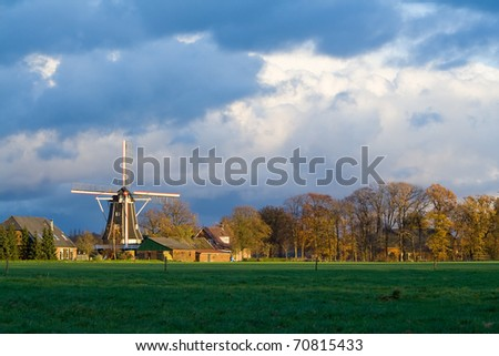 Dutch windmill lighted by the sun on a stormy Autumn afternoon