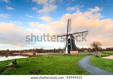 Dutch windmill over blue sky with white clouds before the sunset