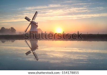 Dutch windmill reflected in river at sunrise, Groningen, Netherlands