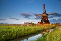Dutch windmill reflected in river in morning sunrise sunlight,  Holland