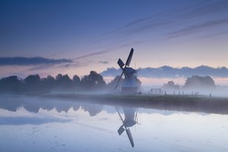 Dutch windmill reflected in river in sunrise fog, Groningen, Netherlands