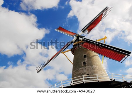 dutch windmill with red blades on a blue and white cloudy sky background