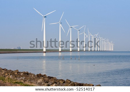 Dutch windmills along the coastline, mirroring in the calm sea
