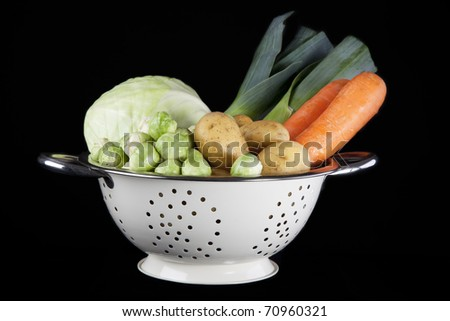 Dutch winter vegetables including carrots, potatoes, brussel sprouts, cabbage and leeks.  All in white colander on black background.
