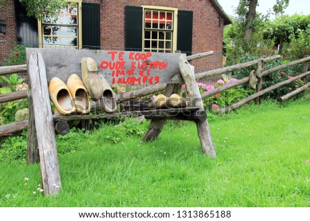 Dutch wooden shoes for sale on the side of a rural street in Holland. Text on wooden sign translation: For saleold clogs 1 pair 5 Euro1 clog 3 Euro