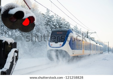 Dutch yellow and blue train riding in the snow