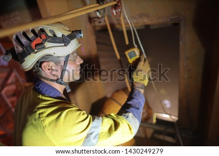 Duty of care certified site safety officer inspector conducting inspecting gas testing atmosphere detector hanging on entry and exit confined space manhole door while friend are working inside