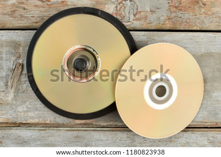 DVD discs on old wooden background. Stack of compact disks on rustic wooden surface. Outdated digital data storage. #1180823938