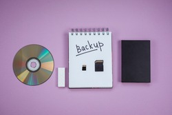 dvd, flash drive, hard drive, sd card and Notepad with the words backup are on a lilac background. Top view, backup concept